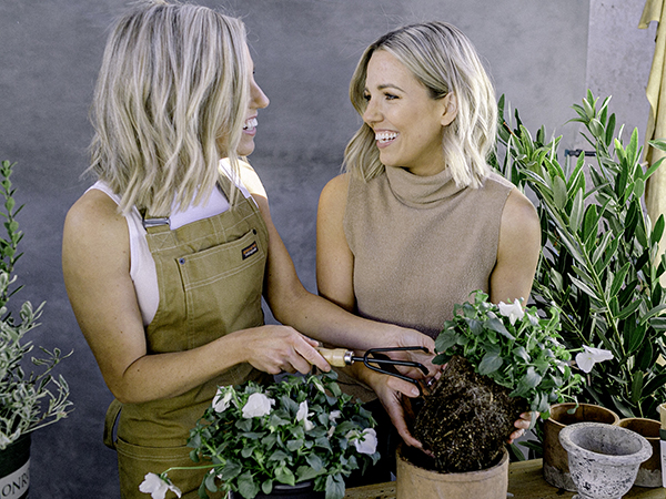 Twin sisters, those plant ladies, planting potted flowers