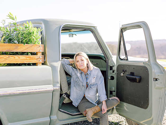 Heather from Those Plant Ladies sitting in a broken-down pickup truck.