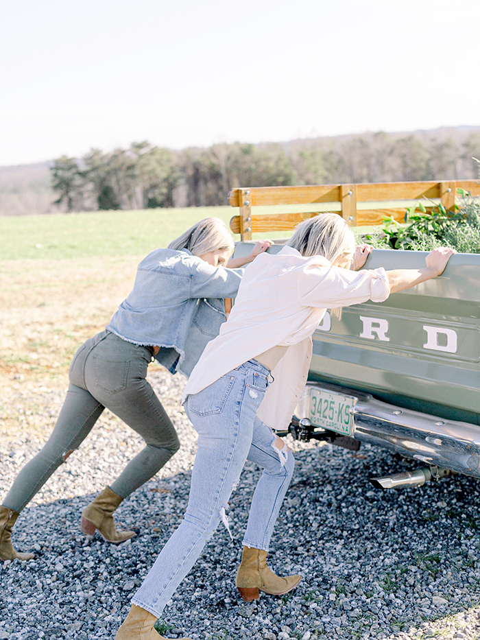 Those Plant Ladies Fawn and Heather pushing a green Ford pickup truck.