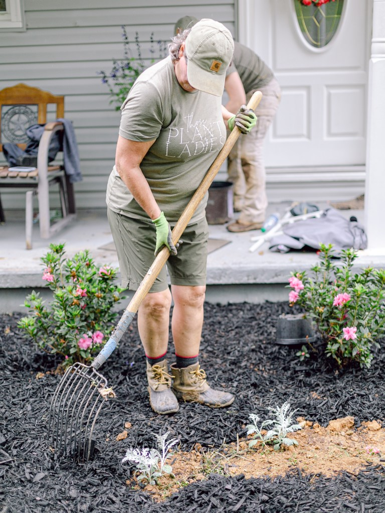 A member of Those Plant Ladies spreading mulch at an installation.