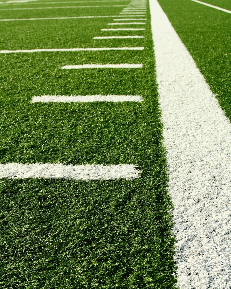 A close-up of a football field with painted hashmarks.