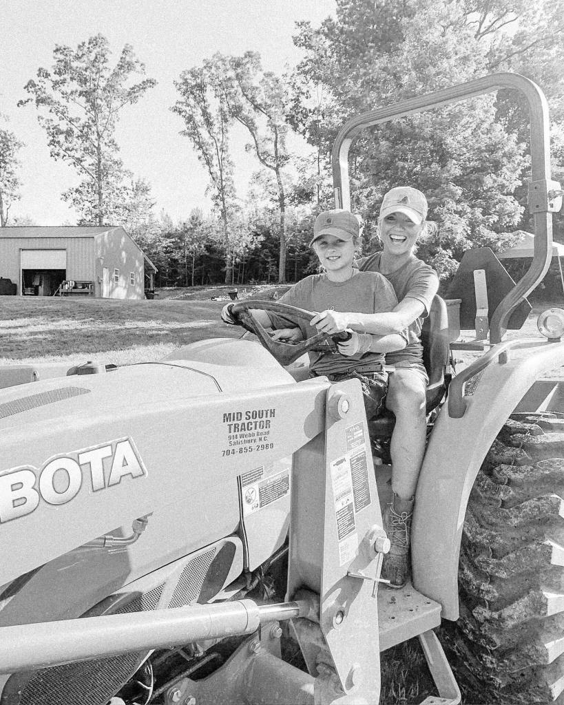 Fawn of Those Plant Ladies teaching a young girl to drive the Kubota tractor.