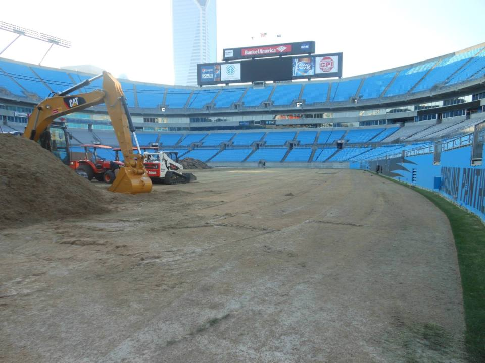 The turfgrass being installed with large equipment at the Carolina Panthers' Stadium.