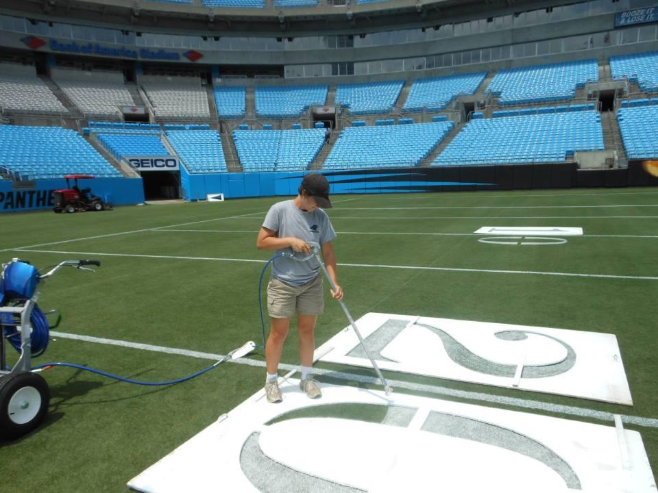 Alexa of Those Plant Ladies painting the 20-yard line at the Carolina Panthers' stadium.