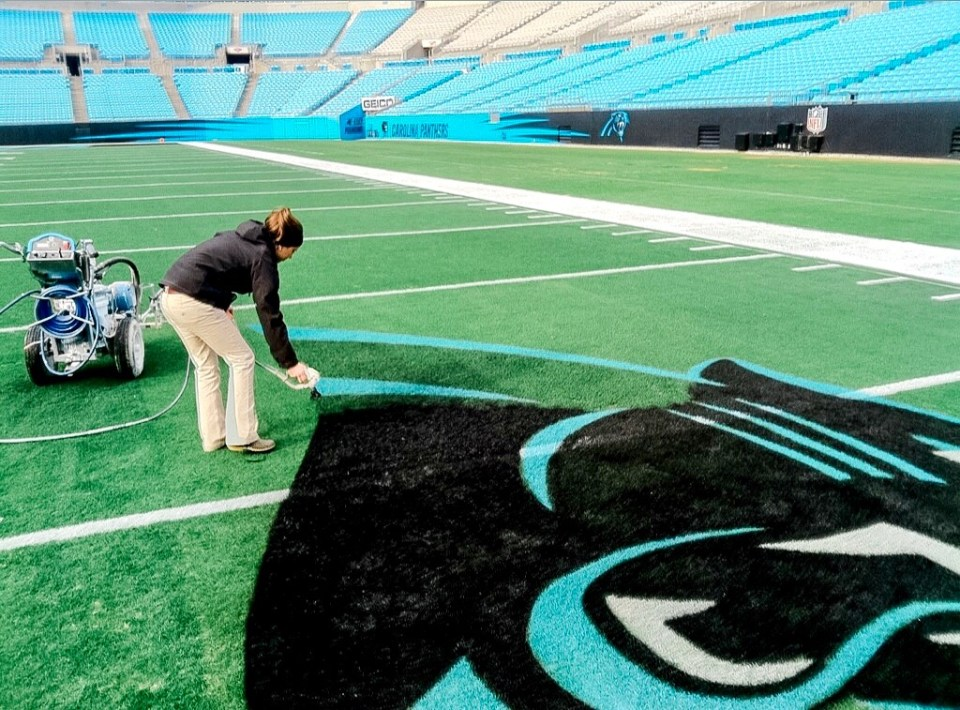 Fawn of Those Plant Ladies painting the lines of the logo for the Carolina Panthers.