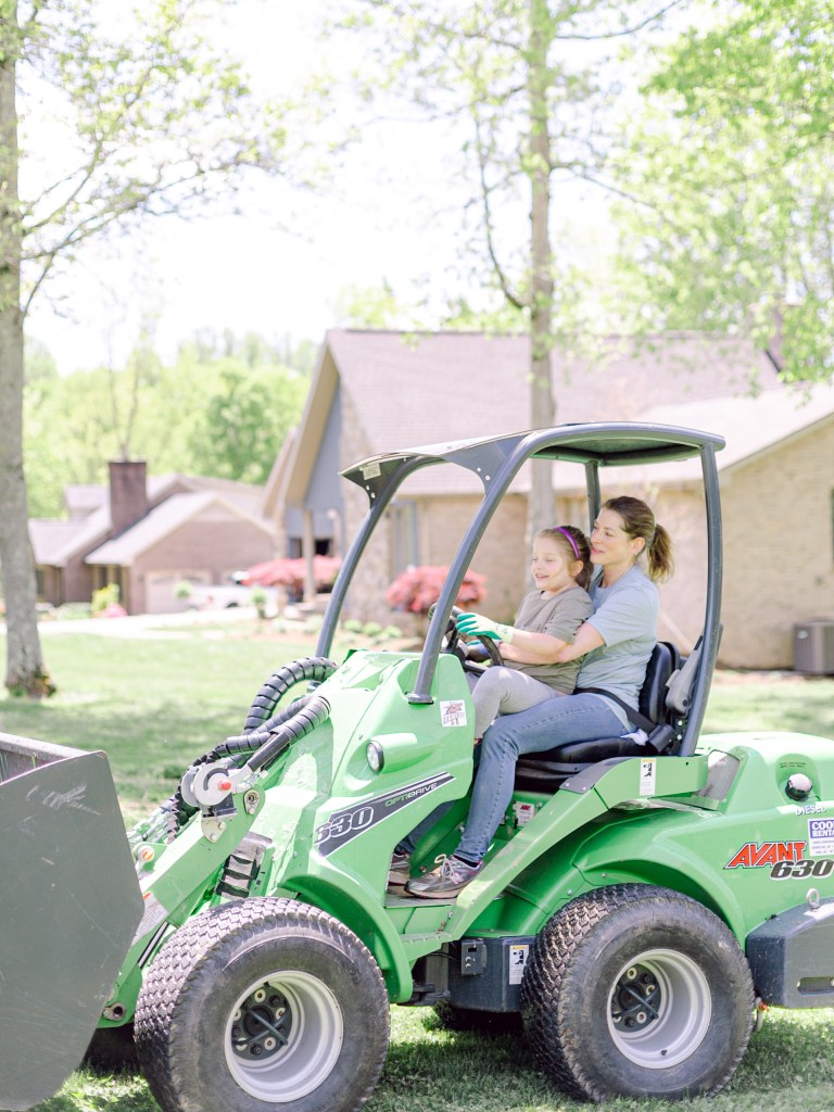 One of the crew members of Those Plant Ladies at a landscape installation, showing her daughter how to drive a tractor.