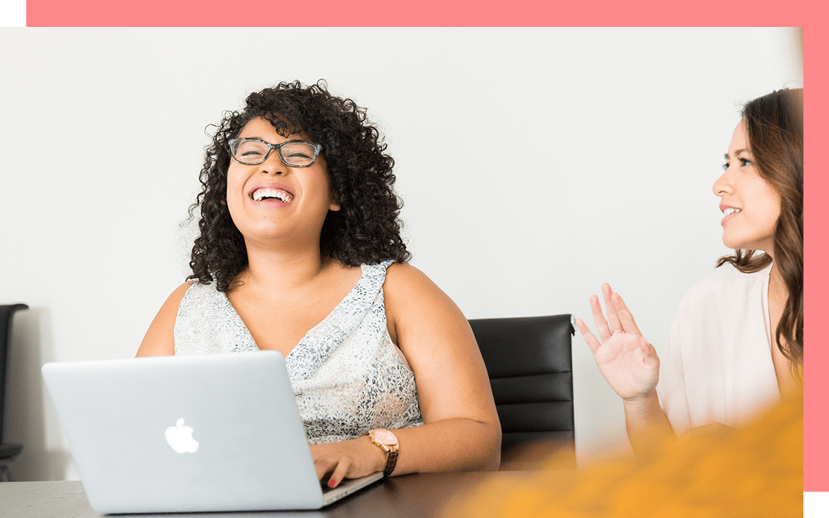 Woman working on laptop and laughing