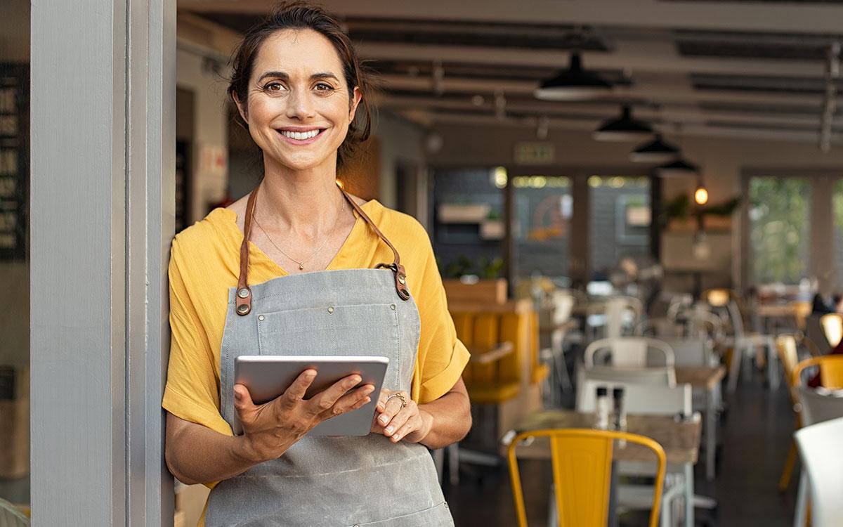 Woman chef standing at the door of her restaurant