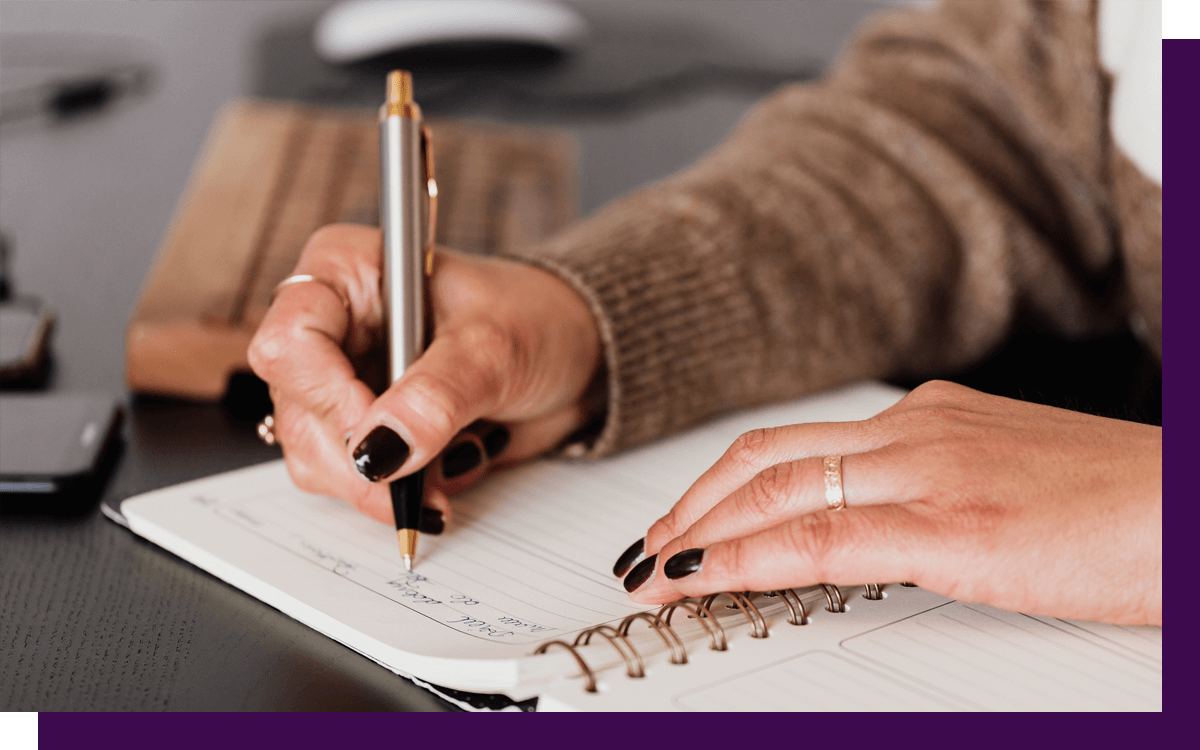 close up of woman writing in journal and practicing mindfulness