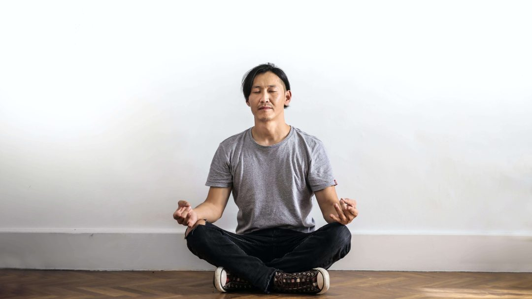 Person meditating, while sitting on the floor