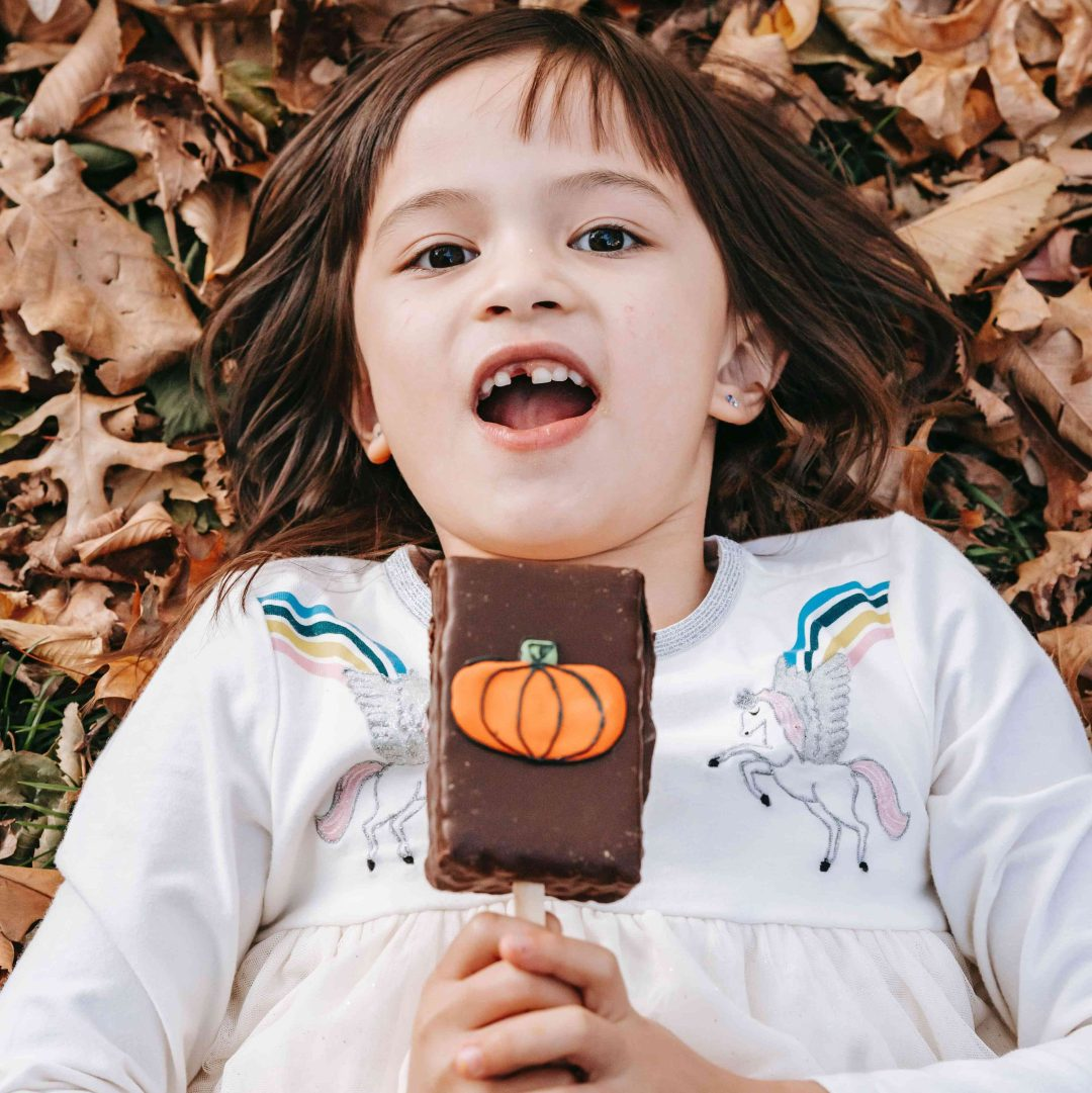 Child smiling and holding a chocolate with a pumpkin decoration