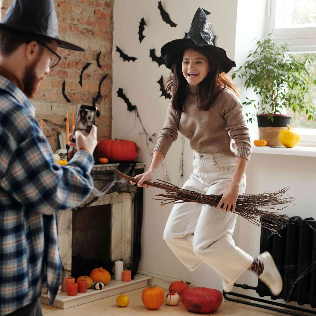 Person taking picture of another person on a broom next to Halloween decorated wall