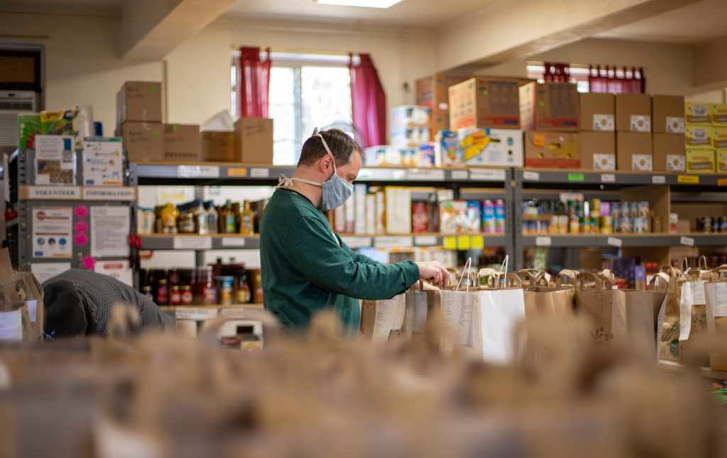 Image shows a person in a warehouse collecting food packages for a food program