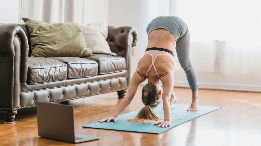 Person on the yoga mat in front of the laptop, participating in online yoga class