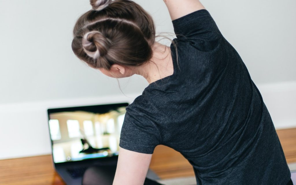 A person participating in online stretching class in front of their laptop