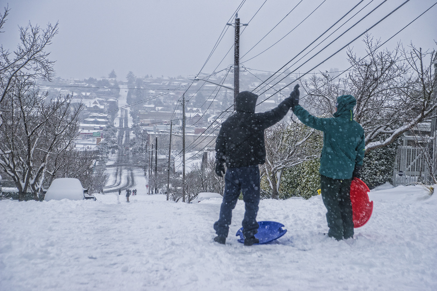 "Minutes before sledding, two friends ""high-five"" each other at the top of the hill on McGraw Street, Magnolia, Seattle (February 13, 2021)."