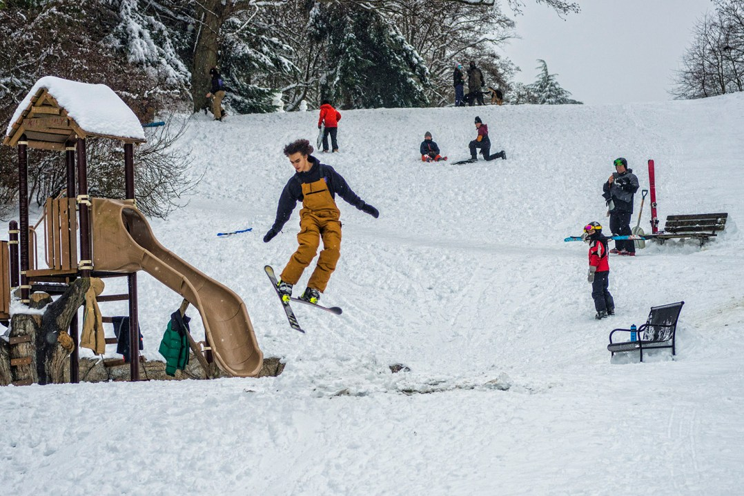 After snowboarding down the hill, this fellow scores a few seconds of airtime after launching from a makeshift ramp made of snow at Lawton Park, Magnolia, Seattle (February 14, 2021).