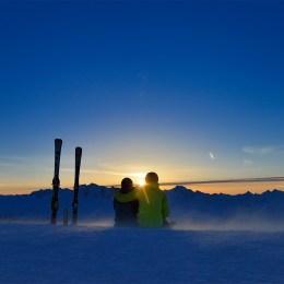 Romantisch: Zwei Skifahrer geniessen den Sonnenaufgang.