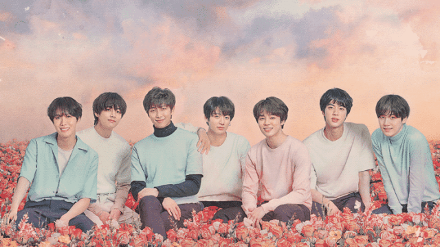 [Image Description: BTS are sitting in a bed of pink, red and yellow flowers. They're all wearing pastel coloured shirts, and there are clouds behind them that are coloured purple and orange. From left to right: J-Hope, V, RM, Jungkook, Jimin, Jin, Suga - Source: Ticketmaster]