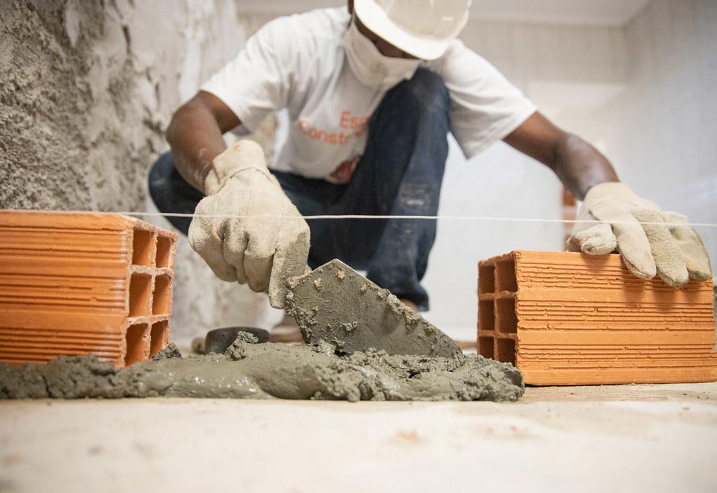 Man laying bricks from a wall.
