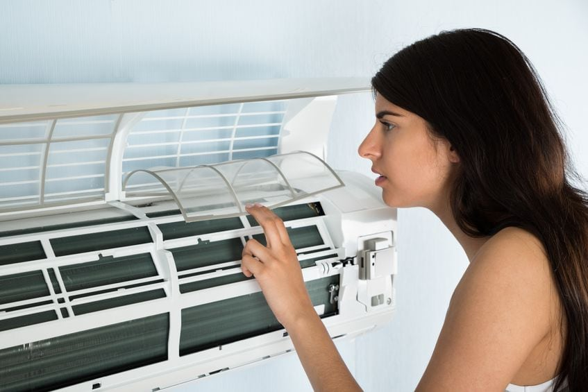Girl examining broken AC unit