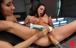 Brunette gropes her own breasts while fucked by a machine and her lady friend rubs her off