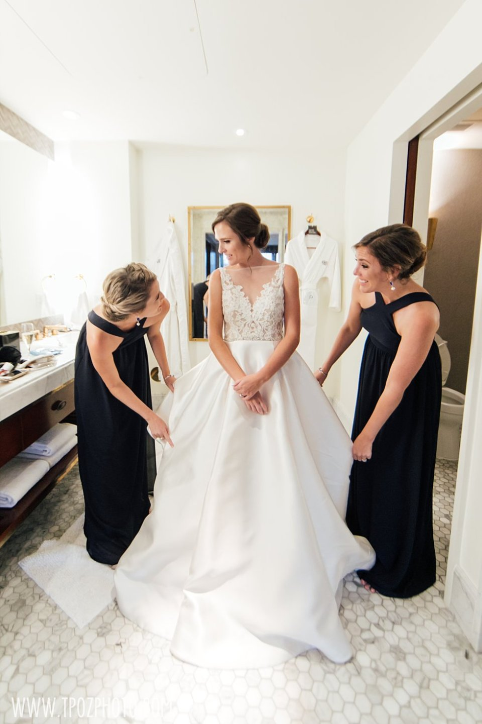 Bride's final touches in her Lazaro gown •  tPoz Photography • www.tpozphoto.com