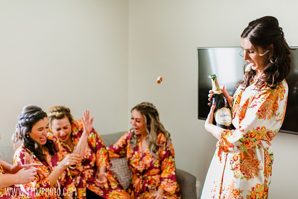 Bride popping champagne  •  tPoz Photography •  www.tpozphoto.com