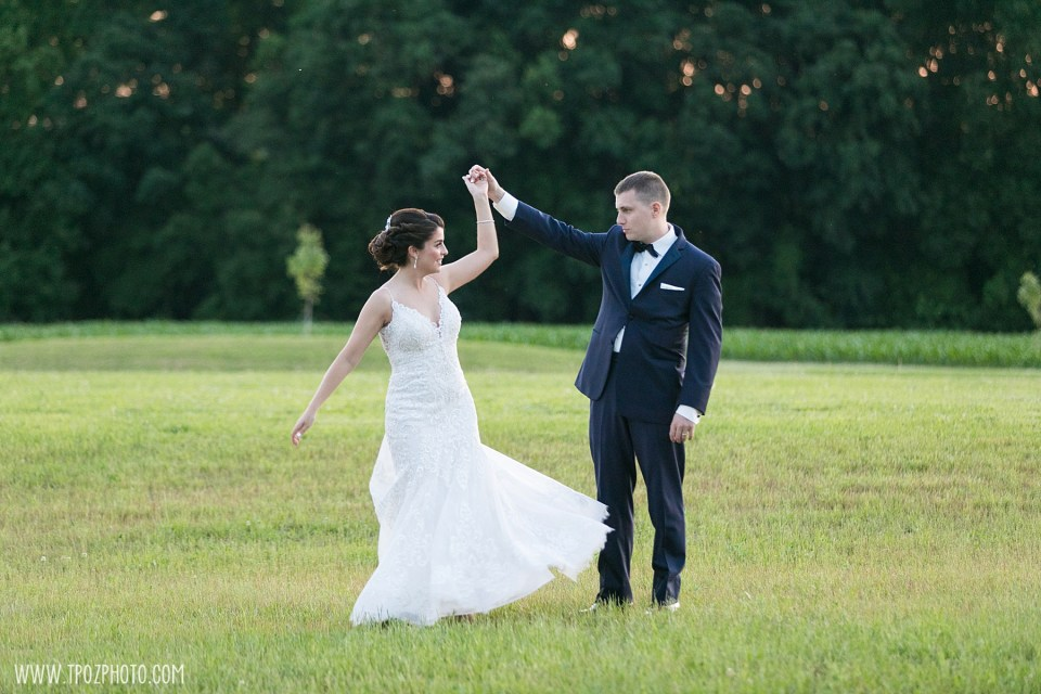 Bride twirling with her groom in a field  - Maryland Wedding Photographer