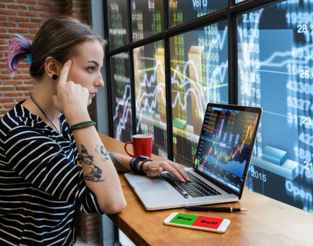 business-financial-and-forex-concept-hipster-young-woman-freelancer-thinking-about-her-job-and-using-computer-laptop-showing-trading-graph-with-the-stock-exchange-trading-graph-screen-ba