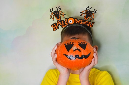 Young boys poses for the yearbook with a pumpkin at his classroom Halloween party for promotion of book sales.