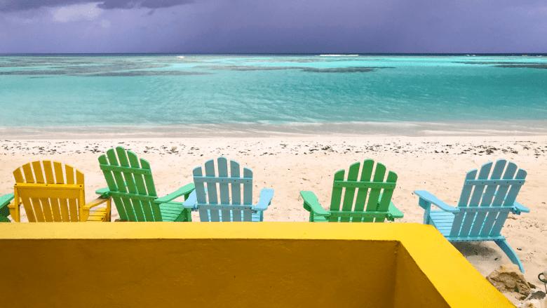 Gekleurde stoeltjes op het strand bij Cows Wreck