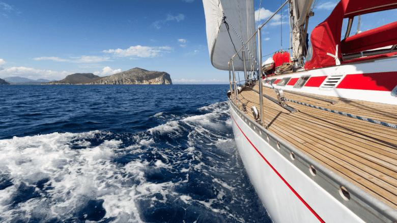 Boot aan het zeilen Sardinie met eiland aan de horizon