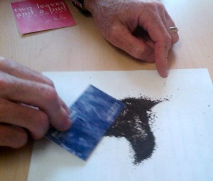 Richard pushes around tiny fragments of tea from an open bag of Lipton Tea.