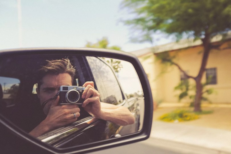 man taking photo reflected in wing mirror