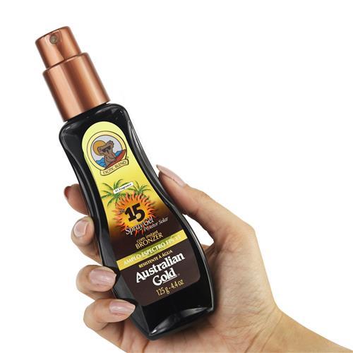 Mão segurando o protetor solar em spray da Australian Gold FPS 15.