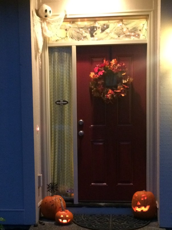 A dimly lit red front door with a fall wreath. Above it to the left is a cloth ghost; at the foot of the door are three pumpkins, two of which are carved with traditional spooky faces and lit with candles.