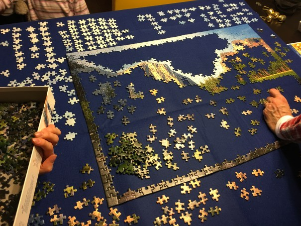 A large jigsaw puzzle depicting El Capitan and Yosemite Valley is partially assembled.