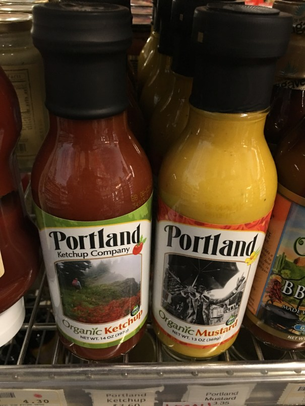 Two rows of Portland Organic ketchup and mustard bottles sit adjacent to one another on a shelf at a vegan grocery