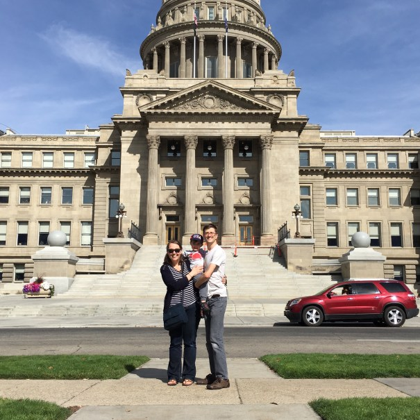 Andrle, Nick, and Theo stand in front of the Idaho State Capitol as a red SUV drives into frame.