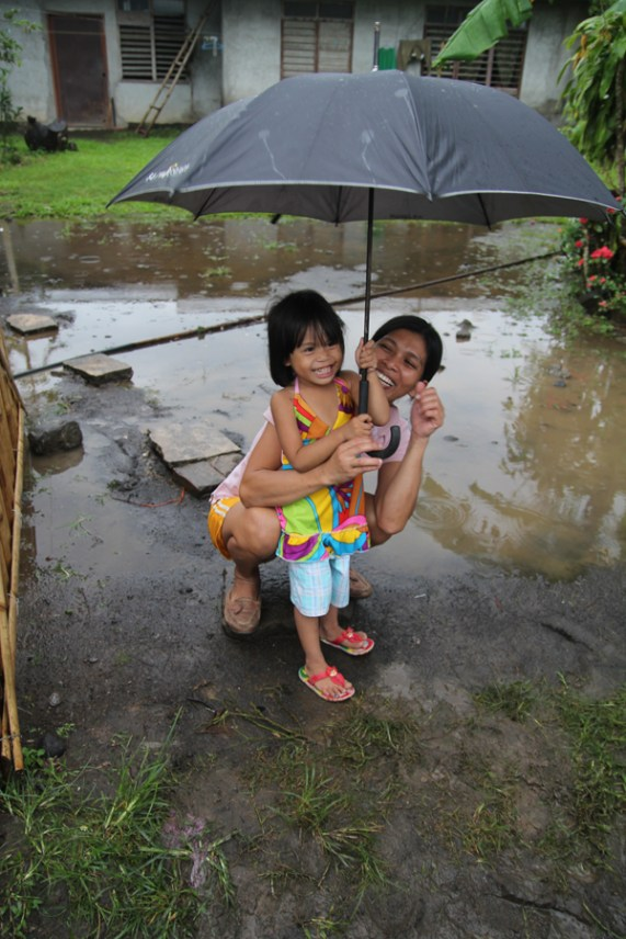 Hilda, mother of a CFCA sponsored child, playing with her daughter, Ryza, in the rain in the Philippines.