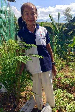 Flor helps tend an herbal and vegetable garden with other elders near Quezon City, Philippines.