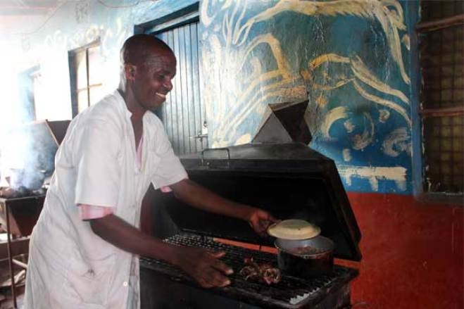 Peter, 47, from Kenya roasts goat meat for his customers.