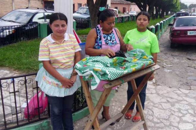 Julia and her daughters, Maria (left) and Ondina (right), sell bread they made using a family recipe.
