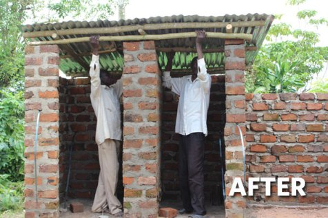 Moses (left) gets help from his friend Lawrence in building the latrine.