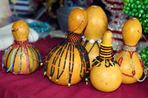 Teresia adds beads to these dried gourds, creating beautiful home decorations.