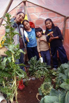 Florencia and three of her children inside her vegetable garden.