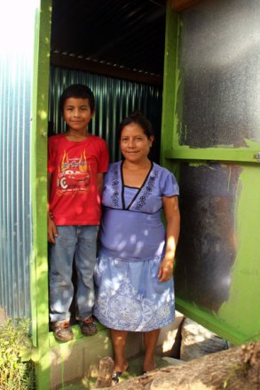 Hector and his grandmother Rosa stand in front of their new latrine.