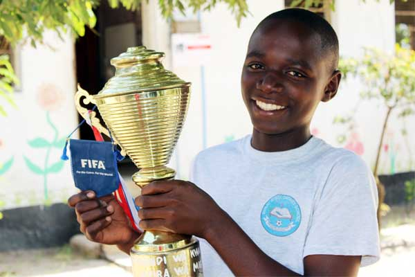 Haji proudly holds a soccer trophy he won.