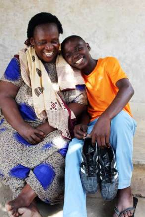 Haji, holding his prized soccer shoes, shares a joyful moment with his grandmother, Tendeje.